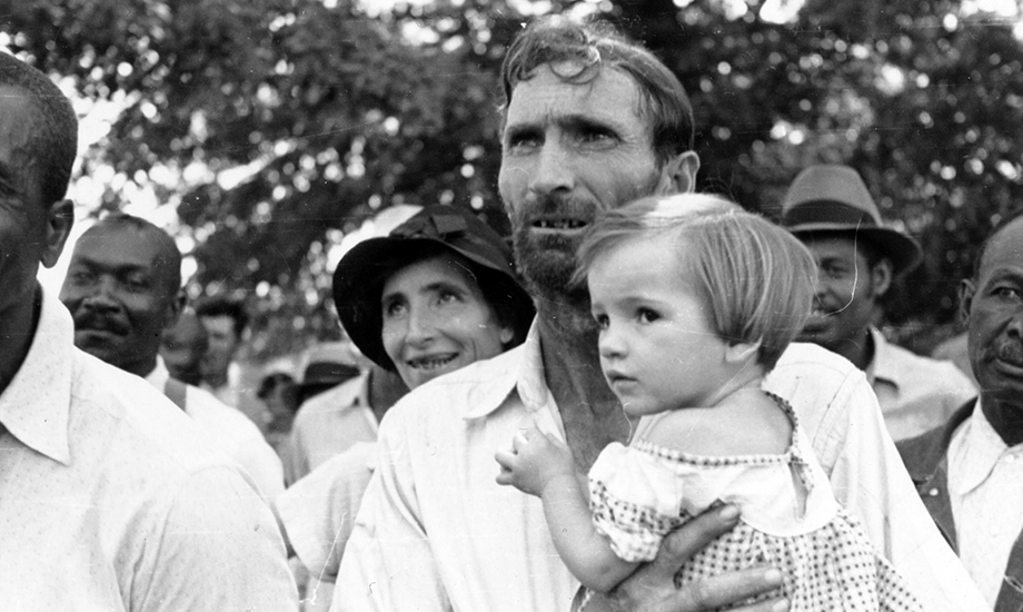 Man holds a child at an outdoor Southern Tenant Farmers Union  meeting.